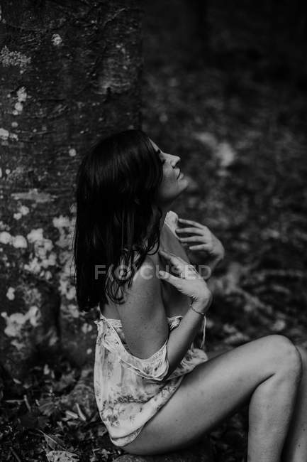 Shy sensual woman sitting on stone in forest — Stock Photo