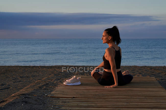 Back view of flexible woman twisting body while sitting crossed legged on seashore and doing yoga in evening — Stock Photo