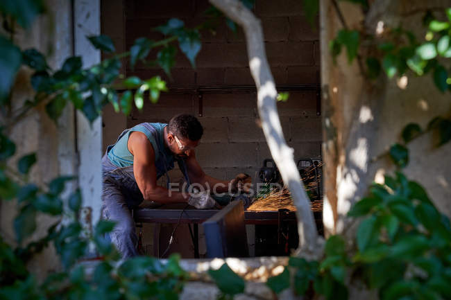 Blick von Baumzweigblättern eines Arbeiters in Schutzbrille und Handschuhen, der während der Arbeit in der Werkstatt mit einem Schleifer mit Funkenflug Metall schneidet — Stockfoto