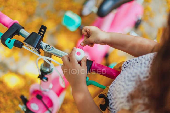 Imagem cortada de menina andando de bicicleta e olhando para baixo no parque — Fotografia de Stock
