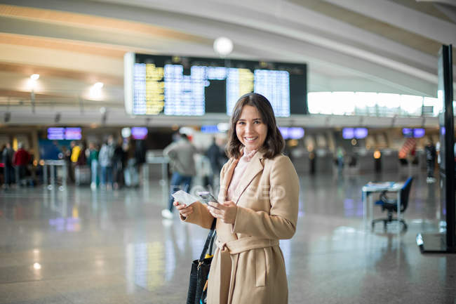 Woman using smartphone at airport — Stock Photo