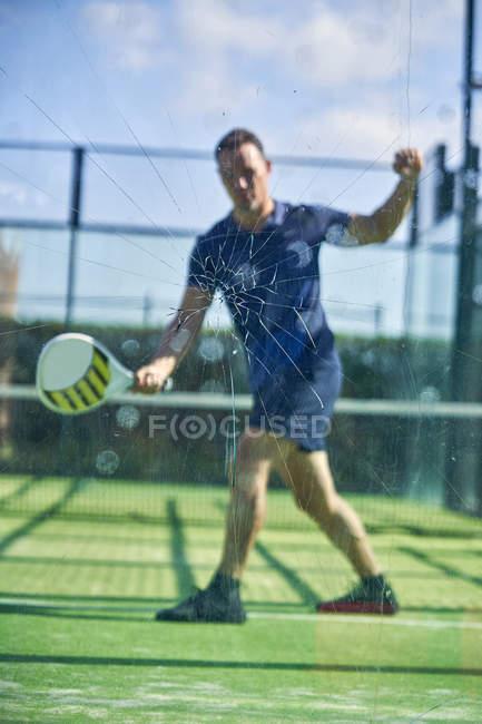 Взрослый мужчина в спортивной форме играет в теннис в солнечный день на корте — стоковое фото