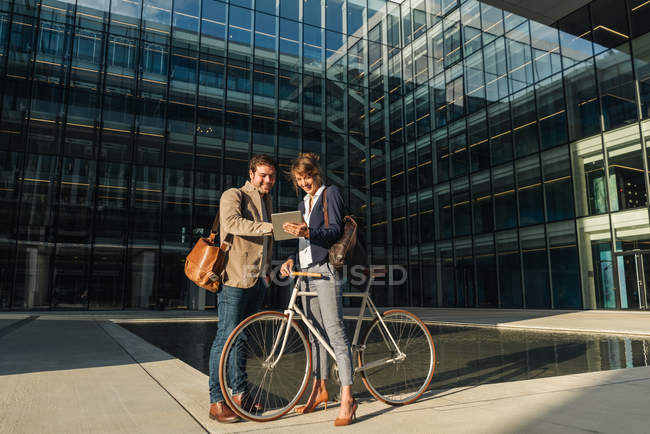 Cheerful man and woman with bicycle smiling and looking at a tablet while communicating outside office building on modern city street — Stock Photo