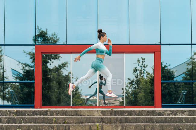 Сфокусована жінка в спортивному одягу біжить швидко до камери під час тренування на асфальтній дорозі зі скляним будинком на задньому плані — стокове фото