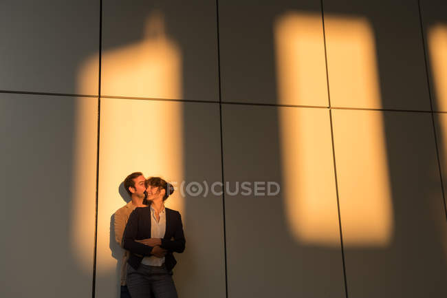 Businessman embracing and kissing girlfriend while standing outside modern building after work — Stock Photo