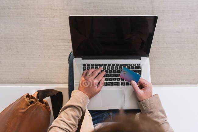 Imagen recortada del empresario usando tarjeta de crédito y portátil mientras se sienta en la calle de la ciudad y paga por las compras en línea. - foto de stock