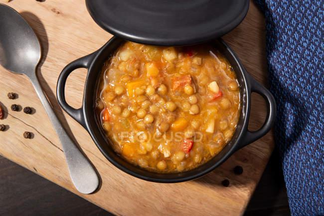 Традиционный суп из чечевицы с ножками в черной запеканке на столе. — стоковое фото