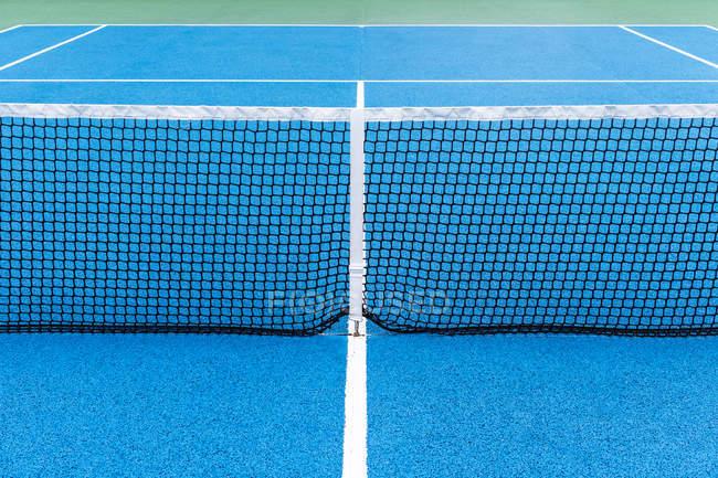 Detalhe da quadra de tênis ao ar livre azul e verde com rede preta . — Fotografia de Stock