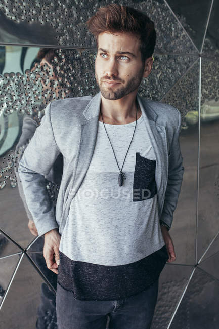 Fashionable handsome man in stylish gray jacket and casual t shirt standing and looking away with wall on background — Stock Photo