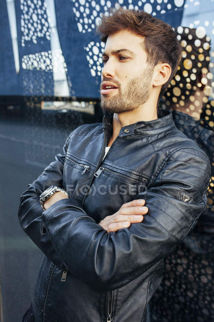 Confident fashionable male in casual stylish outfit leaning on modern glasses wall and looking away — Stock Photo