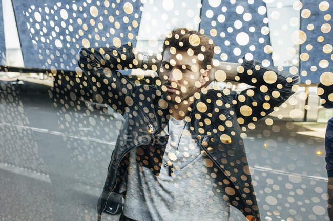 Сквозь украшенное стекло вид стильного молодого человека в кожаной черной куртке, стоящего с руками на затылке на городской улице — стоковое фото