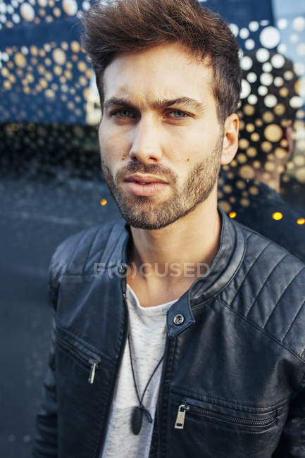 Confident fashionable male in casual stylish outfit leaning on modern glasses wall and looking at camera — Stock Photo