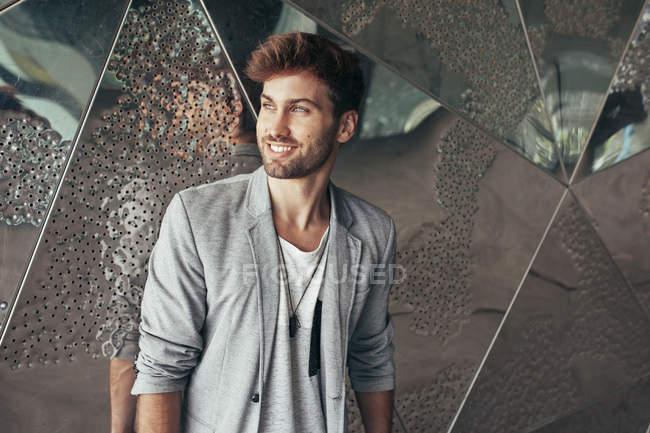 Homme beau à la mode en veste grise élégante et t-shirt décontracté debout et regardant loin avec mur sur fond — Photo de stock