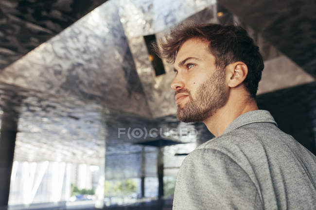 Alla moda bell'uomo in elegante giacca grigia e maglietta casual in piedi e guardando lontano con parete sullo sfondo — Foto stock