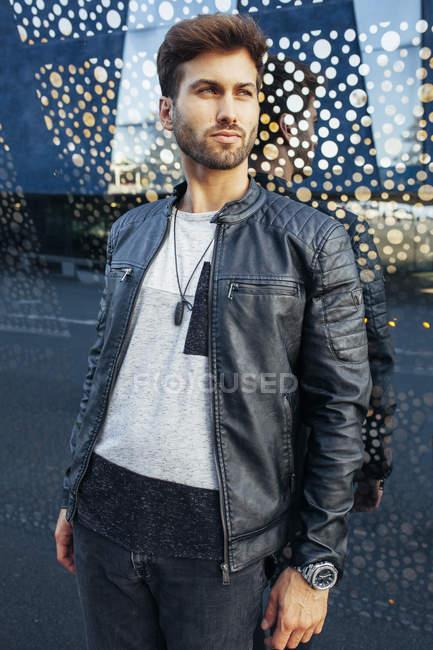 Fiducioso maschio alla moda in abbigliamento casual elegante appoggiato sulla parete occhiali moderni e guardando altrove — Foto stock