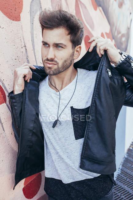 Уверенный красивый мужчина в модном черном кожаном пиджаке стоит с рукой на затылке и смотрит в сторону с граффити-стеной на заднем плане — стоковое фото