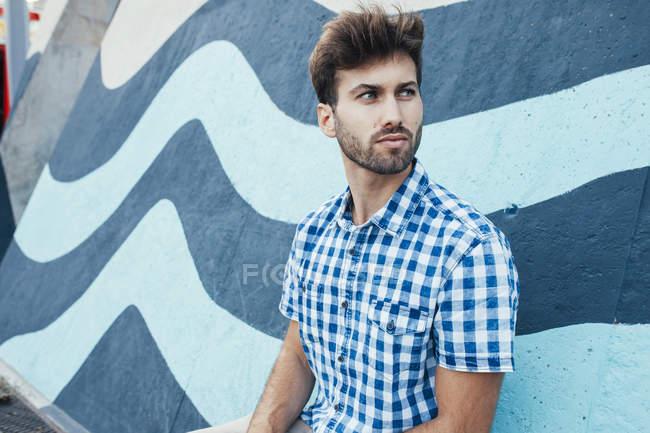 Joyeux jeune homme en chemise à carreaux décontractée regardant loin avec mur peint sur fond — Photo de stock