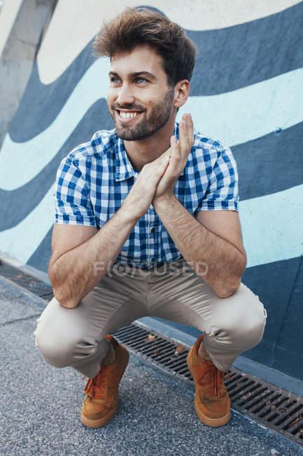 Веселий молодий чоловік у звичайній сорочці з молюсків і кросівках сидить і озирається з розфарбованою стіною на задньому плані. — стокове фото