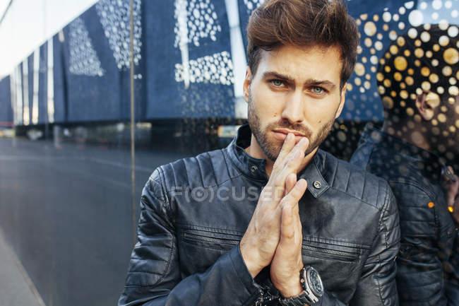 Fiducioso maschio alla moda in abbigliamento casual elegante appoggiato sulla parete occhiali moderni e guardando la fotocamera — Foto stock