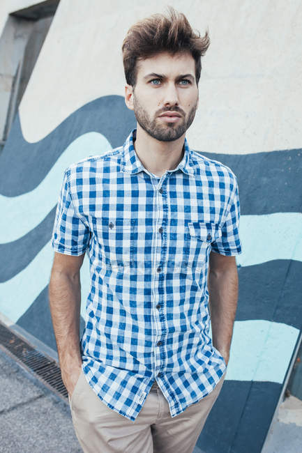 Cheerful young male in casual plaid shirt looking away with painted wall on background — Stock Photo