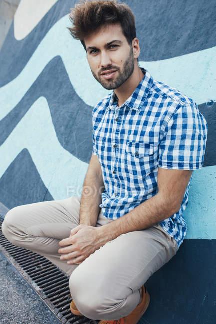 Joyeux jeune homme en chemise à carreaux décontractée et baskets accroupi et regardant la caméra avec mur peint sur fond — Photo de stock