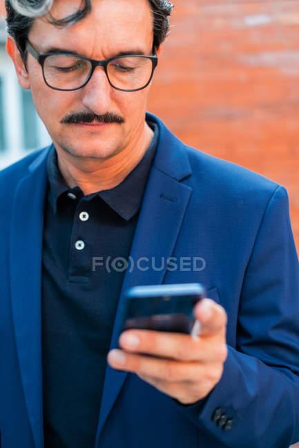 Концентрированный пожилой офисный работник с усами в формальной одежде просматривает мобильный телефон с кирпичной стеной на размытом фоне — стоковое фото
