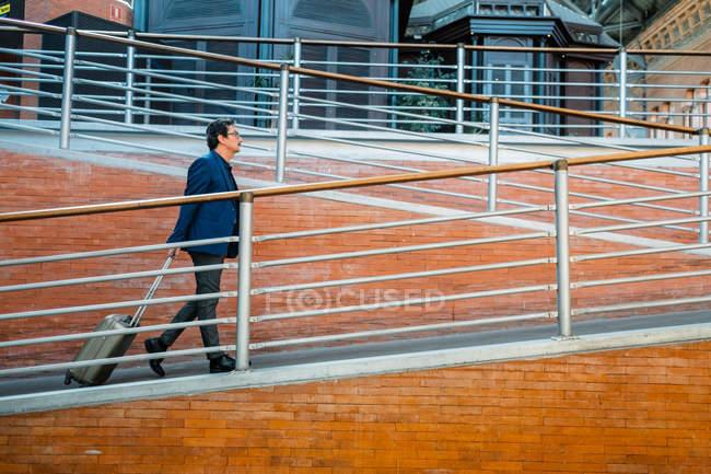 Vue latérale du beau touriste masculin en costume de style formel allant sur rampe en brique avec valise à l'extérieur — Photo de stock