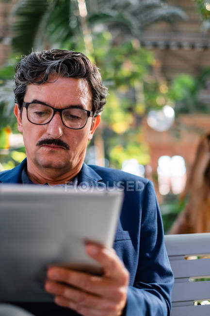 Alter gutaussehender Mann nutzt digitales Tablet im Freien — Stockfoto