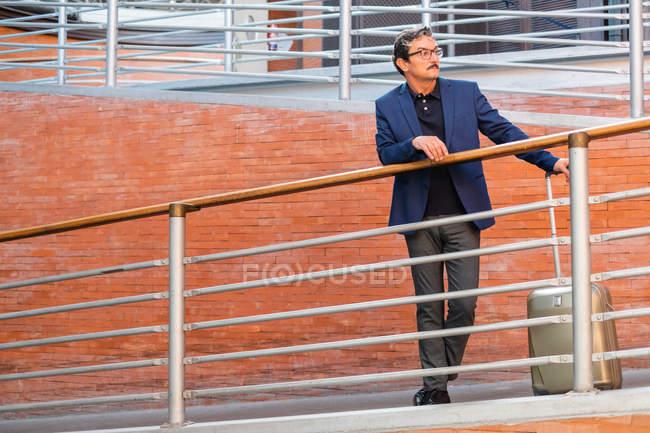 Voyageur âgé avec bagages marchant sur la rampe — Photo de stock