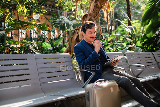 Aged handsome man using digital tablet outdoors — Stock Photo