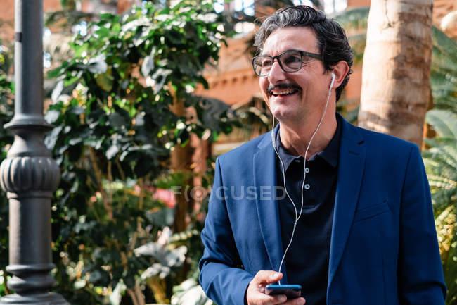 Hombre de negocios envejecido usando teléfono inteligente con auriculares y sonriendo - foto de stock