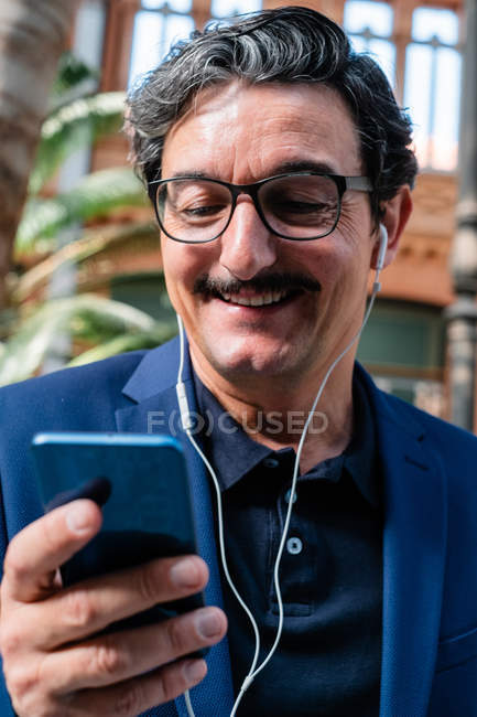Aged businessman using smartphone with headphones and smiling — Stock Photo