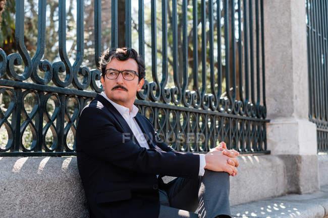 Высокопоставленный мужчина в стильных очках и формальной одежде сидит с крестом на скамье и смотрит в сторону — стоковое фото