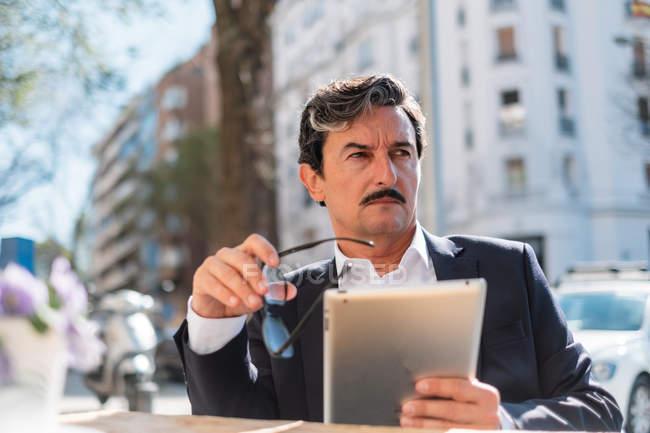 Пожилой человек, использующий гаджет во время отдыха в кафе — стоковое фото