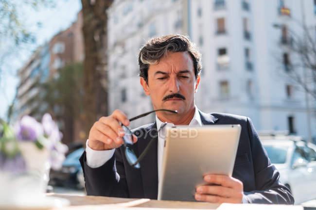 Entrepreneur masculin âgé sérieux dans des vêtements de style d'affaires travaillant avec une tablette numérique tout en étant assis au café extérieur sur fond flou — Photo de stock