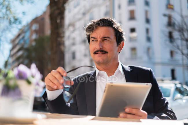 Пожилой мужчина использовал гаджет во время отдыха в кафе — стоковое фото