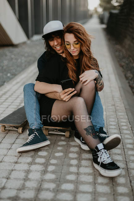 Cool trendy couple sitting on road with skateboard using mobile phone in city — Stock Photo