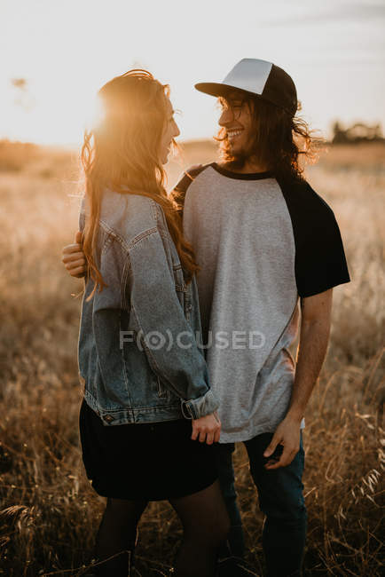 Giovani adolescenti alla moda che abbracciano felicemente astuto in piedi in remoto campo rurale con calda luce del tramonto — Foto stock