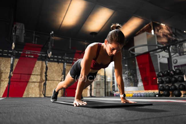 Стройная спортивная женщина стоит в доске в фитнес-студии во время занятий физкультурой — стоковое фото