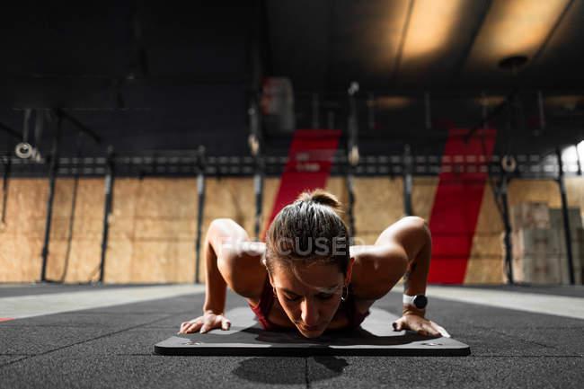 Schlanke, sportliche, konzentrierte Frau, die während des körperlichen Trainings im Fitnessstudio in der Planke steht — Stockfoto