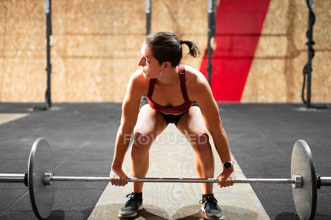Concentrated sportive strong woman preparing for lifting heavy barbell in gym during workout looking away — Stock Photo