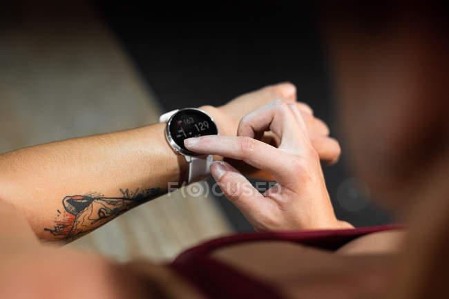 Abgeschnittenes Bild einer tätowierten Frau mit moderner Trackeruhr und Zahlen auf schwarzem Bildschirm während der Kontrollzeit — Stockfoto