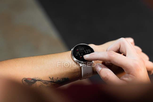 Перекручене зображення татуюваної жінки з сучасним трекер-годинником і номерами на чорному екрані під час перевірки часу — стокове фото
