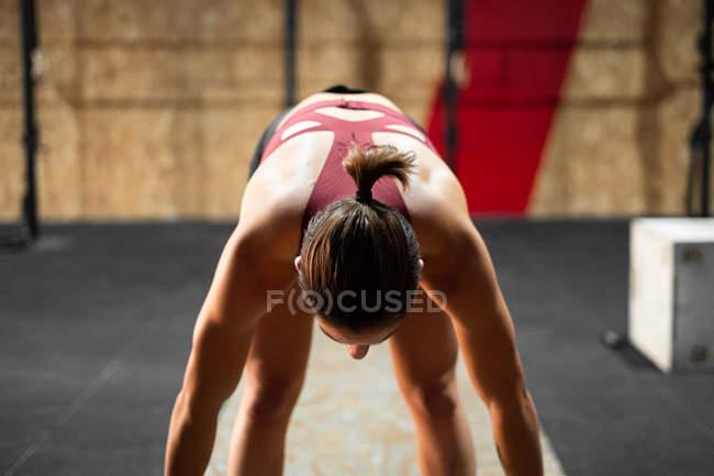 Концентрированная спортивная сильная женщина готовится к подъему штанги в тренажерном зале во время тренировки, отводя взгляд — стоковое фото