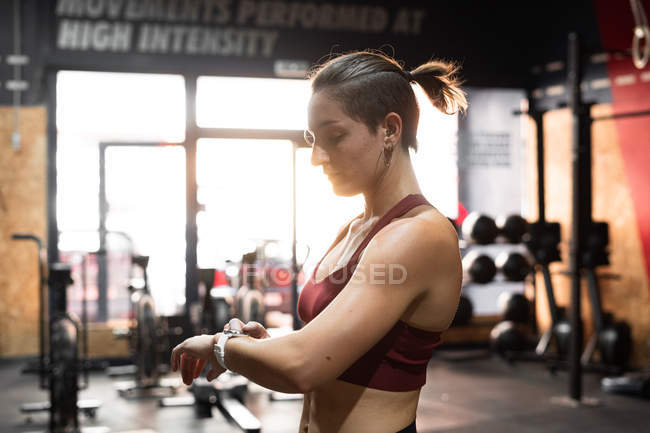 Woman with tattooed hand and modern tracker checking time of sport exercise — Stock Photo