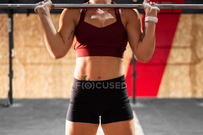 Cropped image of sportive strong woman preparing for lifting heavy barbell in gym during workout looking away — Stock Photo