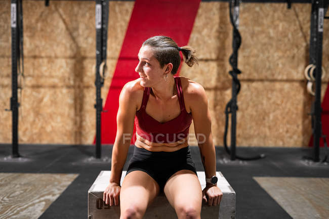 Young tired exhausted sporty female athlete in sportswear relaxing on box between exercises in gym — Stock Photo