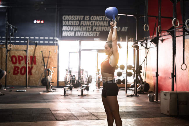 Side view of powerful sportive female athlete lifting kettlebell with both arms above head during physical training in fitness club — Stock Photo