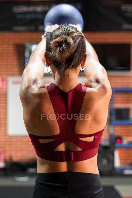 Вид сзади мощной спортсменки, поднимающей колени обеими руками над головой во время занятий физкультурой в фитнес-клубе — стоковое фото