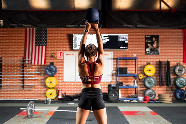 Back view of powerful sportive female athlete lifting kettlebell with both arms above head during physical training in fitness club — Stock Photo